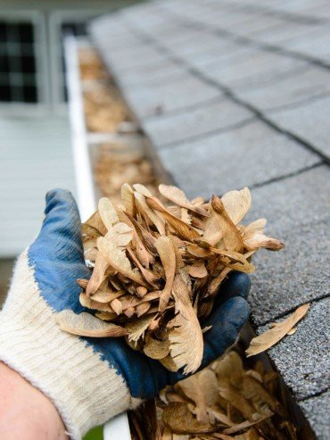 Gutter cleaning in action with gloves